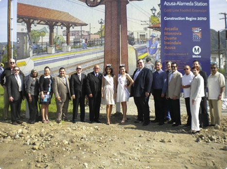 Dignitaries from Azusa and Foothill Extension Authority celebrate new station location in front of Gold Line Billboard.