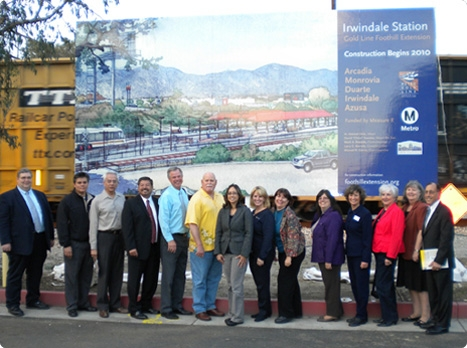 Irwindale leaders and Foothill Extension personnel celebrate new station in front of billboard