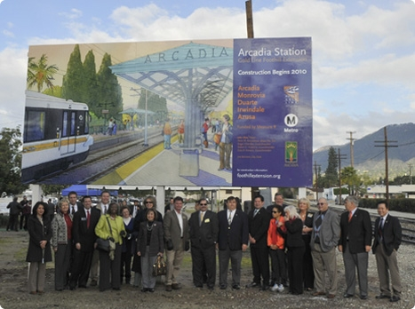 Arcadia City representatives join with Extension authority personnel to celebrate new station site in front of billboard illustration